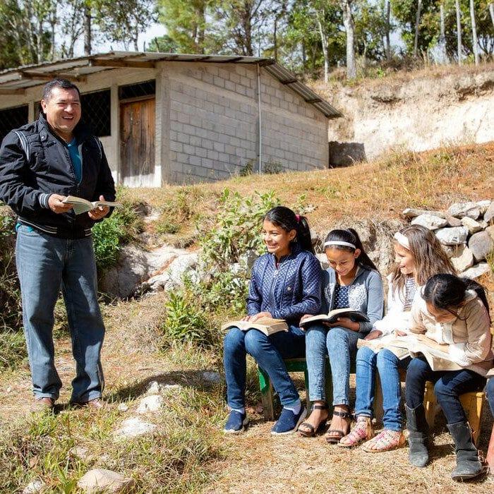 """alt=""""Compassion_20_Jahre_in_Honduras_Kinder_sitzen_auf_einer_Bank_vor_der_Kirchengemeinde"""""""