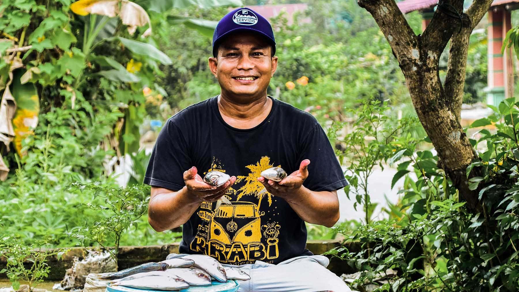 """alt=""""Julius' Familie Indonesien Compassion Deutschland 01 mit Fischen aus einer Kühlbox"""""""