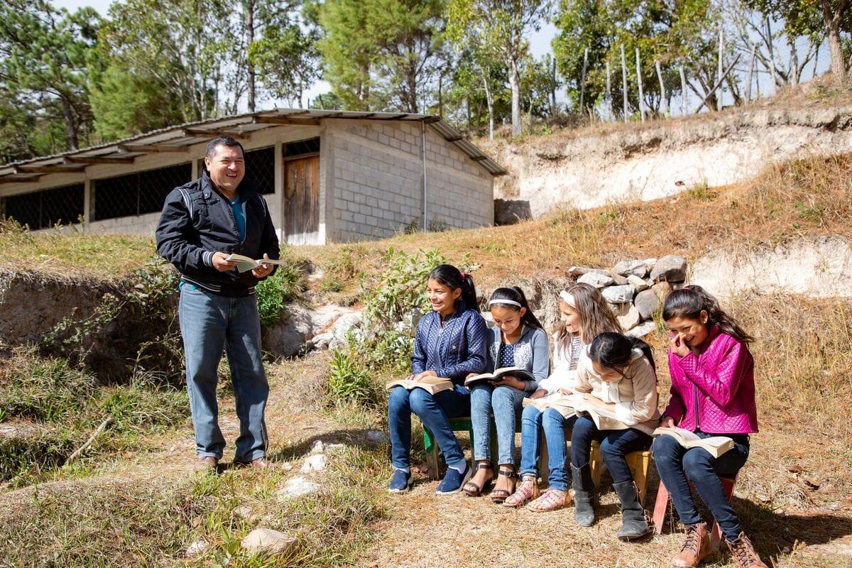 """alt=""""Pastor Genaro in Honduras mit Patenkindern vor der Gemeinde. Kinder lesen Bibel"""""""