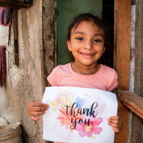 """alt=""""dankbares_Mädchen_mit_Schild_thank_you_COVID-19 hat eine Hungerkrise hervorgerufen"""""""