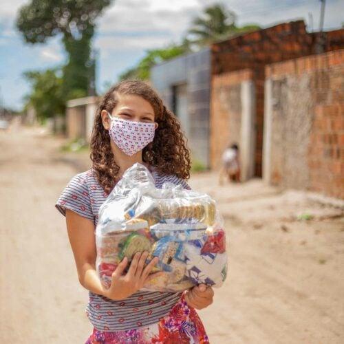 """alt=""""Mädchen_mit_Essenskorb_COVID-19 hat eine Hungerkrise hervorgerufen"""""""